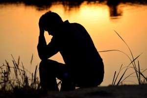 depressed man sitting against the light reflected in the water